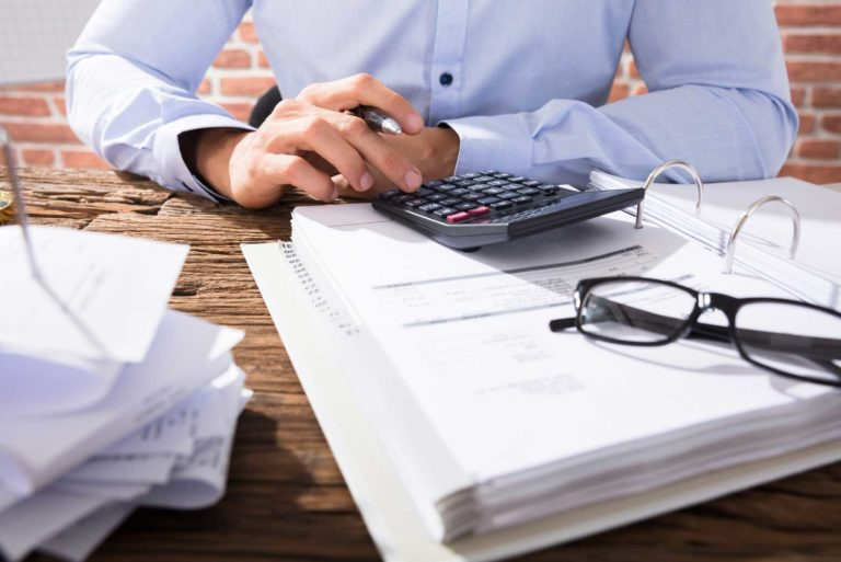 Close-up Of A Business Person Calculating Invoices Using Calculator In Office